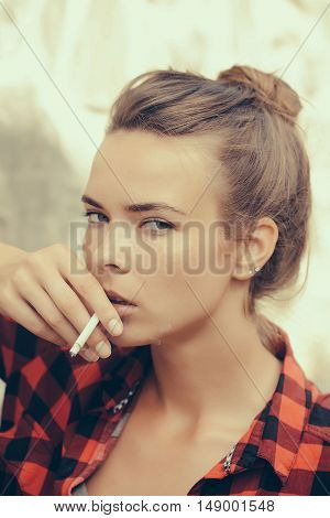 Young girl with pretty serious face in chequered red and black open shirt holding in hand near mouth smoking cigarette on natural background outdoor