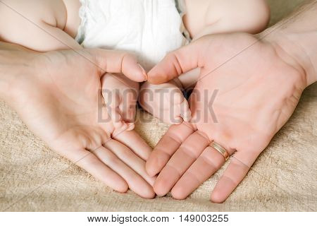 Newborn baby cute tiny feet holding mothers and fathers parents hands in heart shape closeup