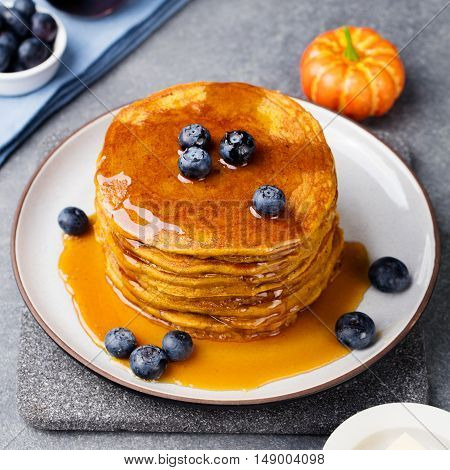 Pumpkin pancakes with maple syrup and blueberries on a plate Grey stone background