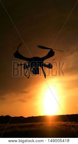3d render quadrocopters silhouette in the background. radio-controlled toy is filming nature. Unmanned flying drone sunset