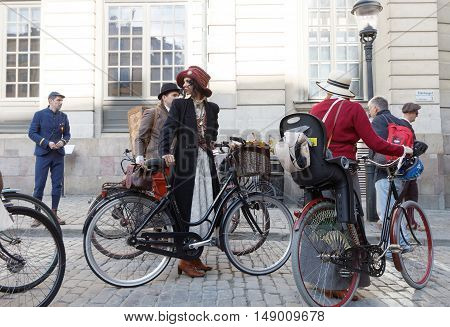 STOCKHOLM - SEPT 24 2016: People with bicycles dressed in old fashioned tweed and dresses in the Bike in Tweed event September 24 2016 in Stockholm Sweden