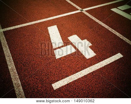Number Four. White Track Number On Red Rubber Racetrack,