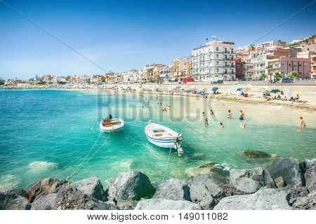 Giardini Naxos, ITALY - July 2016: Group of tourists at the beach of Giardini Naxos, near city Taormina, Sicily, Italy in August, 2015, Italy