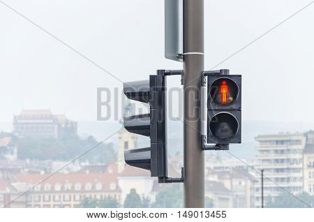 Traffic light on the background of the street. Steady red color. Close-up.