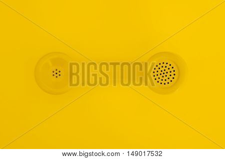 A retro yellow telephone handset centered on a yellow background.