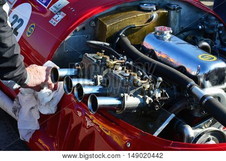 CLUJ-NAPOCA ROMANIA - SEPTEMBER 24 2016: Hand cleans the engine of Stanguellini Formula Junior oldtimer racing car parked in Polus Center parking lot