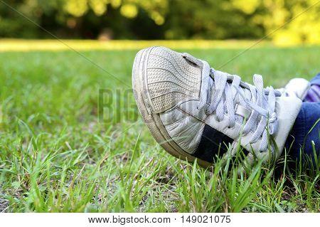 dirtry scuffed tennis shoe lawn green grass
