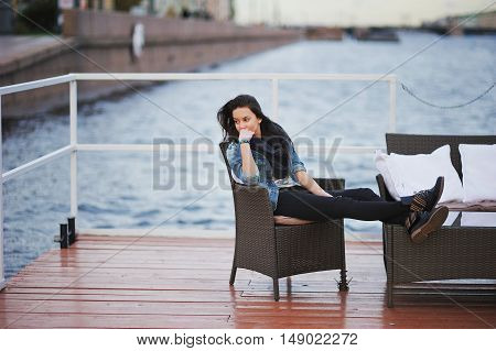 Beautiful long haired student in a blue denim jacket and black scarf pensively sitting in a chair on the pier his legs crossed against the vague shape of embankment in St. Petersburg.