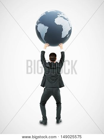 Back view of young businessman holding terrestrial globe on white background. 3D Rendering. International business concept