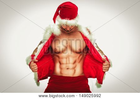Sexy Santa. Young muscular man wearing Santa hat demonstrate his muscles. Isolated on white background.