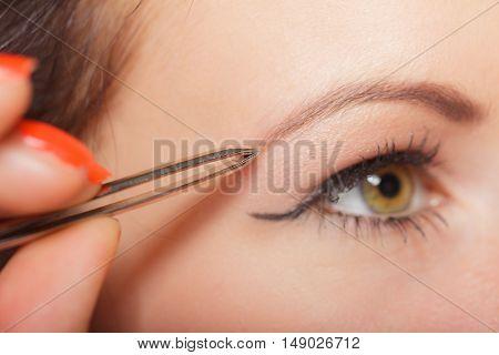 Closeup part of face woman plucking eyebrows depilating with tweezers. Girl tweezing eyebrows.