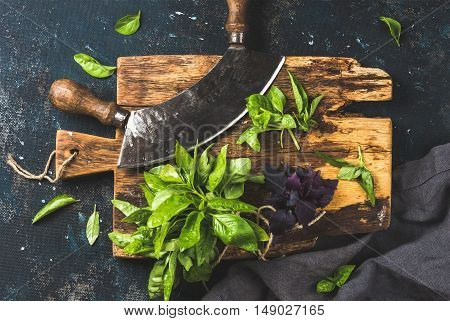 Fresh green basil and vintage herb chopper on rustic wooden board, top view, horizontal composition