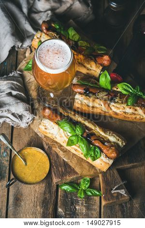 Glass and bottle of wheat unfiltered beer and grilled sausage dogs in baguette with mustard, caramelised onion and herbs on serving board over rustic wooden background, top view, selective focus
