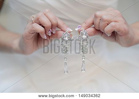 Beautiful bride in white wedding dress is holding earrings in her hands. Beauty model girl in bridal gown for marriage. Female portrait with jewelry. Close-up woman's arms. Cute lady indoors