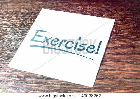 Exercise Sticky Note On Paper Lying On Wooden Cupboard
