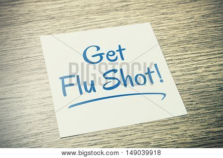 Get Flu Shot Reminder On Paper On Wooden Table