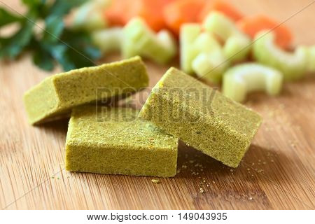 Vegetable bouillon stock or broth cubes on wooden board with parsley and fresh celery and carrot in the back photographed with natural light (Selective Focus Focus on the upper edge of the two cubes in the front)