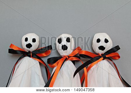 Halloween concept background : Three halloween ghosts DIY made from white tissue paper, black and orange ribbon on gray background