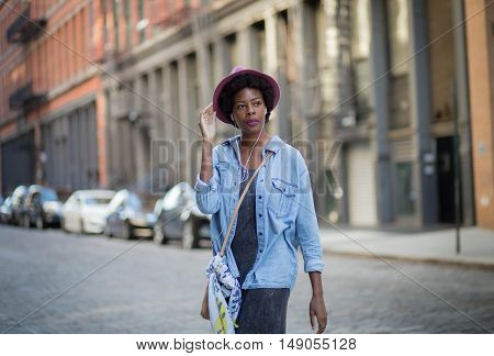 Portrait of young African American woman walking on city street. Photographed in Soho NYC.