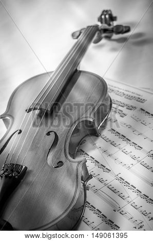 Old violin lying on the sheet of music music concept.