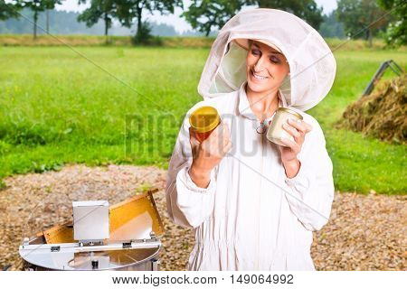 Female beekeeper filling honey with extractor in glass