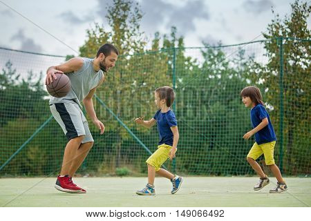 Young children brothers and their father playing basketball in the park