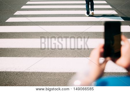 Pedestrian zebra close-up, smartphone on foreground. Photo of people crossing intersection on right place, hands with phone with blank screen. Busy people, urban modern life concept