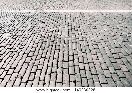 Paving stone square texture. Closeup view on cobblestone road with white lines. Outdoor street background, free space