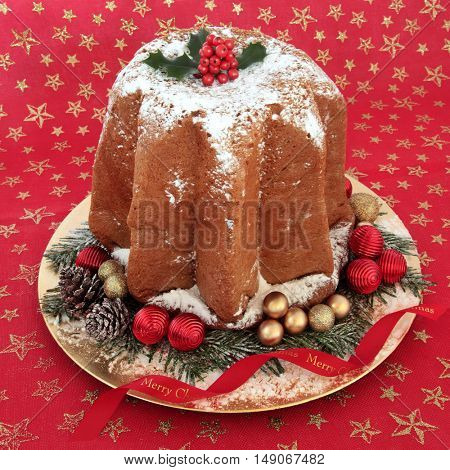 Pandoro christmas cake with holly, icing sugar dusting, bauble decorations on a red and gold star material background.