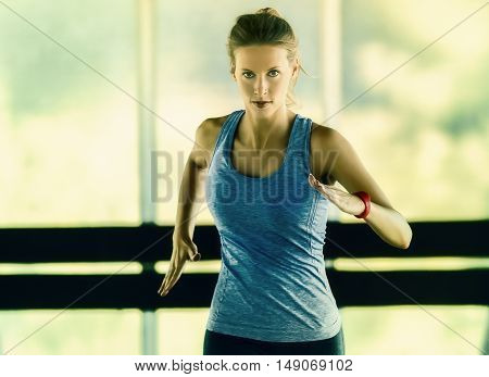 Energetic runnning workout of a young woman in a glass framed corridor. She wears a fitness tracker on her left arm.
