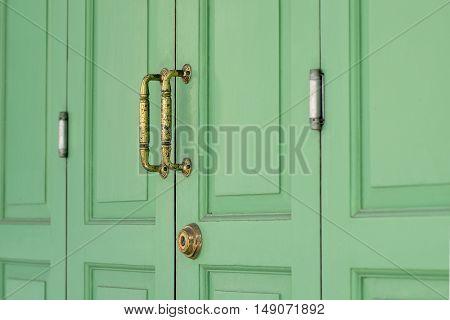Gold brass handle on classic green door