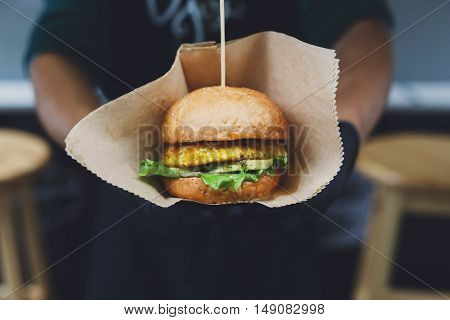 Freshly cooked burger barbecue outdoors in craft paper. Cookout american bbq food. Big hamburger with steak meat and vegetables closeup with chef unfocused at background. Street food, fast food.