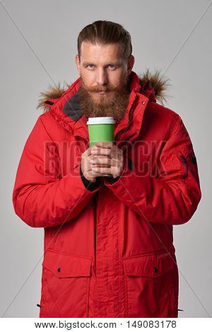 Portrait of a man wearing red winter jacket and holding hot drink in disposable paper cup, studio shot