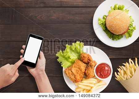 Using Smartphone With Burger, French Fries And Fried Chicken Set On Wooden Background