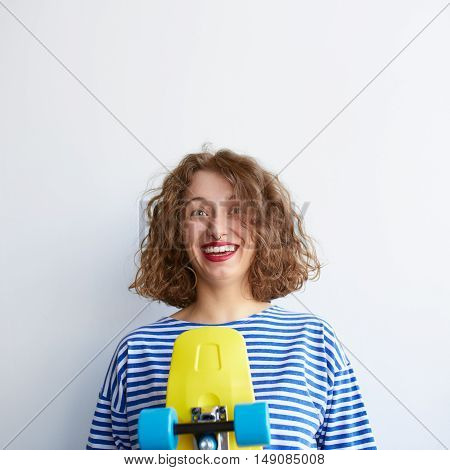 Brunette happy teenage girl in hipster outfit and striped shirt holding a yellow skateboard having and idea with copy space. Nerdy curly hair young woman isolated on white background