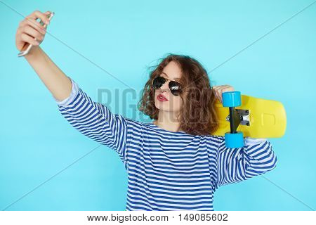 Pretty cool young woman in sunglasses with bright yellow skateboard taking picture self portrait on smartphone over vibrant blue turqoise background
