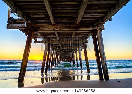 Sunset at Henley Beach viewed from under the jetty