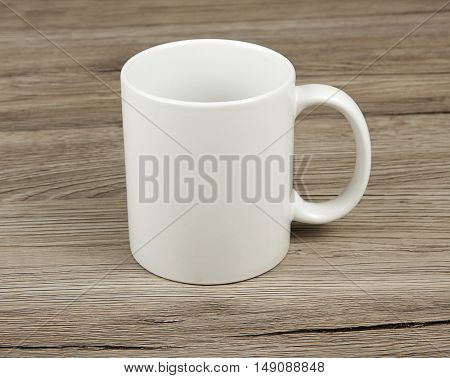 White cup with shadow on a wooden background