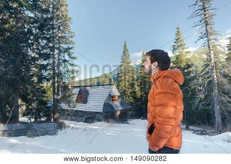 Handsome young man lis ooking at astonishing view in valley with mountain hut and conifer forest