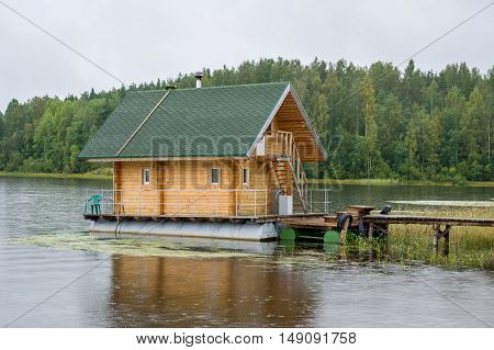 Floating big wooden sauna house is docked at the pier on Ladoga lake. Karelia, Russia.
