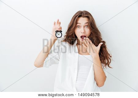 Scared young woman holding alarm clock and looking at camera over white background