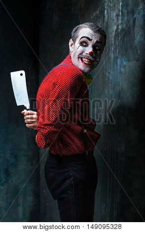 The scary clown holding a knife on dack. Halloween concept of horror and murderer