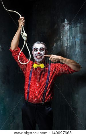 The scary clown and rope for hanging on dack. Halloween concept of horror and murderer