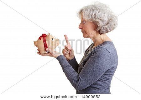 Elderly Woman Admonishing Piggy Bank