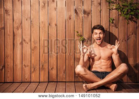 Handsome young smiling man sitting and showing okay sign over wooden background