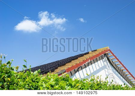 Roof renovation with black tiles in the summer
