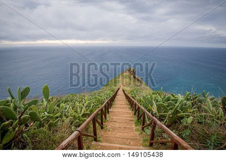 Long wooden steps path from Cristo Rei statue to the ocean cape, surrounded by cactus plants. Ponto Garajau, Madeira island, Portugal.