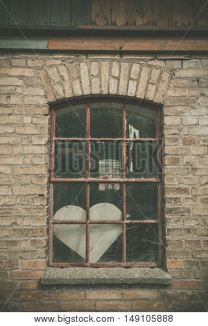Forgotten love heart in a window on an old building