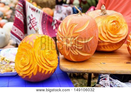 Big orange flower carved pumpkins, close up, traditional ornament carpet in Moldova