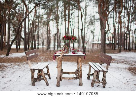 Table Made Of Pine In Snowbound Forest In Winter With Red Wedding Table Setting. Winter Catering Con